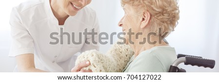 Smiling nurse lying a warm blanket on her elderly patient sitting in a wheelchair in a daycare center #704127022