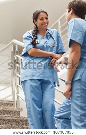 Smiling nurse talking with a colleague in hospital ward