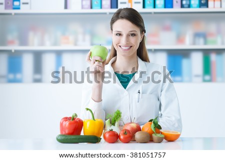 Smiling nutritionist in her office, she is holding a green apple and showing healthy vegetables and fruits, healthcare and diet concept