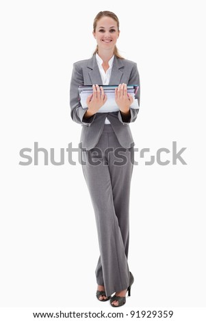 Smiling office employee holding pile of paperwork against a white background