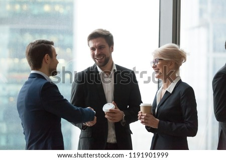 Smiling office workers talk having casual conversation, get acquainted during meeting, excited colleagues handshaking introducing at coffee break at briefing, happy workers greeting shaking hands