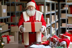 Smiling old funny bearded Santa Claus wearing hat and costume holding Merry Christmas present gift box looking at camera standing in workshop warehouse. Xmas delivery concept. Portrait.