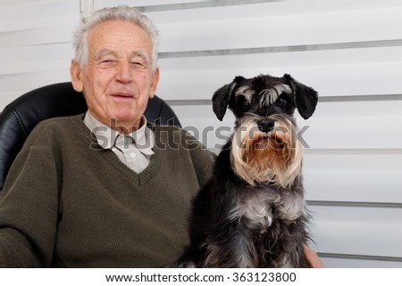 Smiling old man and  black Miniature Schnauzer dog