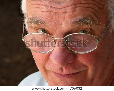 smiling old man peers over his glasses