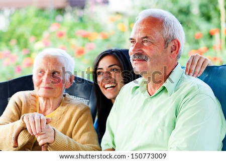 Smiling old man visiting her elderly mother in the nursing home