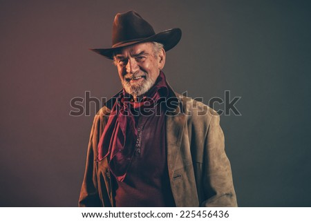 Smiling old rough western cowboy with gray beard and brown hat. Low key studio shot.