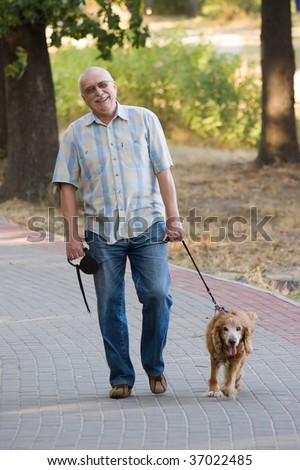 Smiling old senior relaxing in park, and having fun with his dog.