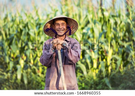 Smiling old Vietnamese farmer with conical hat (non la)