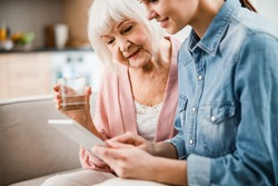 Smiling old woman holding glass of water while girl using modern gadget stock photo