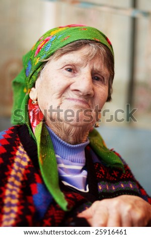 Smiling old woman in colored sweater and orange bright headscarf - stock photo