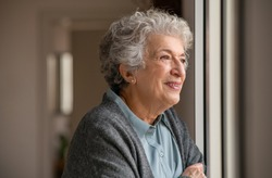 Smiling old woman looking through the window. Happy senior woman standing near window during quarantine due to covid. Retired and contemplative lady wearing sweater while looking outside and thinking.