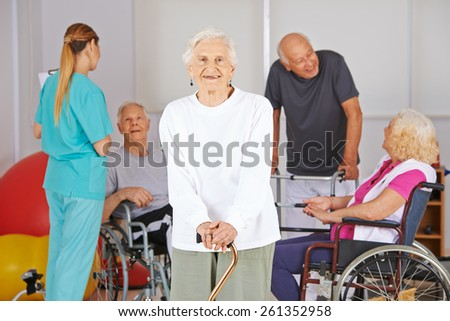 Smiling old woman standing in front of group of senior people in nursing home