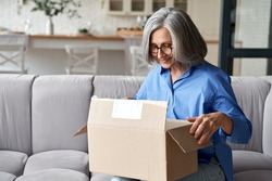 Smiling older adult mature woman customer unpacking parcel concept sitting at home on couch. Happy senior middle aged lady opening online store order receiving gift in postal delivery shipping box.