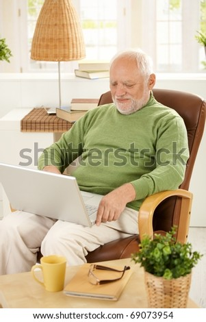 Smiling older man sitting in armchair using laptop computer at home. - stock photo