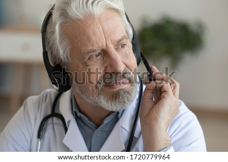 Smiling older senior physician wearing headset with microphone looking away. Online doctor consultation, tele medicine and remote medical assistance, telehealth distance services concept. Close up.