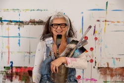 smiling older woman, proud artist, in her fifties with grey hair and black glasses and many paintbrushes