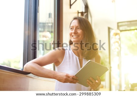 Smiling older woman with tablet looking away