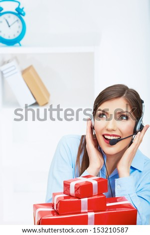 Smiling operator seat at table with red gift box. Happy business woman at office. Female business model posing.
