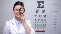 Smiling optometrist looking through magnifying glass and smiling, sight test