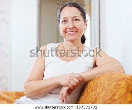 Smiling ordinary mature woman in home interior