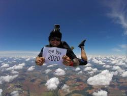 Smiling parachutist holding a written sign: Bye Bye 2020.