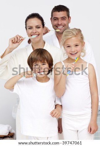 Smiling parents and children cleaning their teeth in bathroom