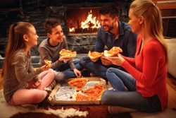 Smiling parents and children have fun and eating pizza together
