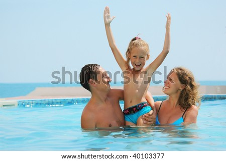 smiling parents play with daughter with hands up in water