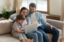 Smiling parents relax on sofa in living room with small 7s son child have fun browsing using modern laptop together. Happy young Caucasian family with little boy kid watch funny video on computer.