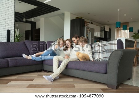 Smiling parents with kids having fun with laptop in cozy living room interior, couple with children son and daughter using computer on sofa at home, happy family relaxing together shopping online #1054877090