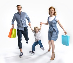 smiling parents with shopping bags holding hands together with excited son isolated on white