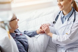 Smiling patient keeping hand of doctor