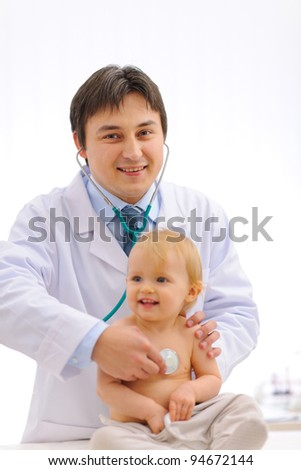 Smiling pediatric doctor checking baby using stethoscope