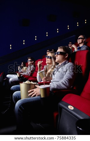 Smiling people in 3D glasses in cinema