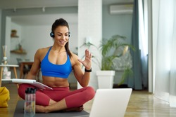 Smiling personal trainer having online consultation with her clients over laptop at home.