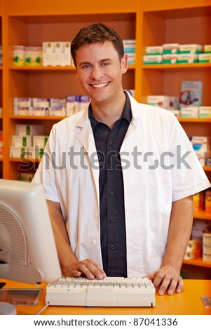 Smiling pharmacist behind the counter of a pharmacy