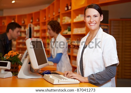 Smiling pharmacist working at computer in a pharmacy
