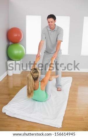 Smiling physiotherapist helping patient doing exercise in bright office