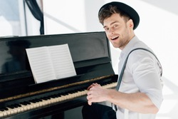 smiling pianist sitting by piano and looking at camera