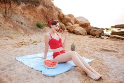 Smiling pin-up girl having great time at the beach eating fruits and candy