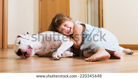 Smiling playful cute little girl hugging big white dog at home