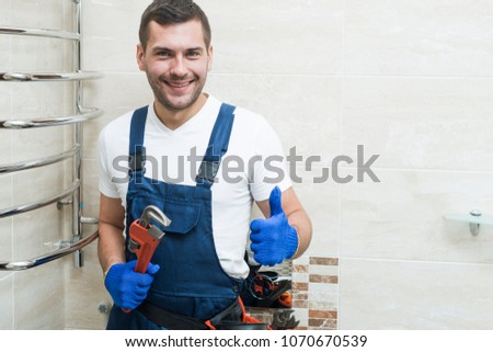 Smiling plumber holding screw-wrench in bathroom