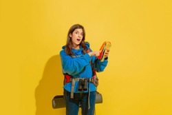 Smiling, pointing on map. Portrait of a cheerful young caucasian tourist girl with bag and binoculars isolated on yellow studio background. Preparing for traveling. Resort, human emotions, vacation.