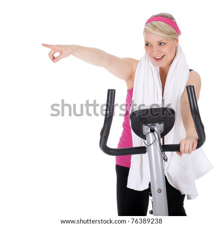 smiling pointing young woman exercising on stationary training bicycle