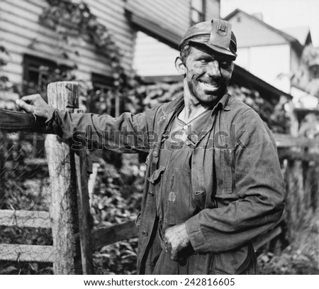 Smiling Polish-American miner, in work clothes and covered with coal dust, arriving home from work in Capels, West Virginia. 1938 photo by Marion Post Wolcott.