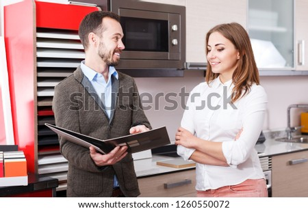 Smiling polite salesman helping young female to choose materials for kitchen furniture in salon