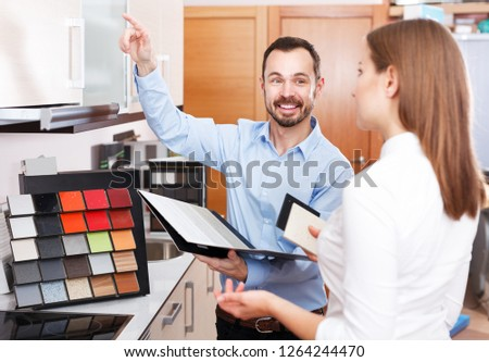 Smiling polite salesman helping young female to choose materials for kitchen furniture in shop