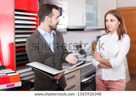 Smiling polite salesman helping young female to choose materials for kitchen furniture in store. Focus on man