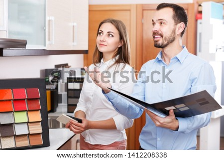 Smiling polite salesman helping young woman to choose materials for kitchen furniture in salon