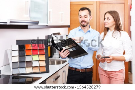 Smiling polite salesman helping young woman to choose materials for kitchen furniture in store